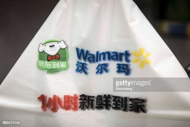 The logos of WalMart Stores Inc and JDcom Inc are displayed on shopping bags inside a WalMart miniwarehouse for the company's onehour delivery...