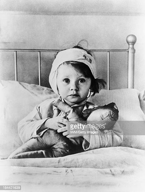 The London Blitz Eileen Dunne aged three sits in bed with her doll at Great Ormond Street Hospital for Sick Children after being injured during an...