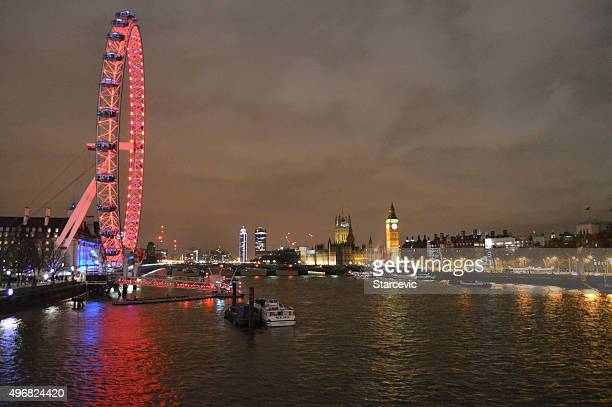the london eye at night - monument station london stock photos and pictures