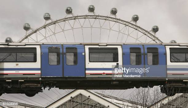 The London Eye ferris wheel is seen behind a London Underground carriage being lifted from the tracks by crane on April 1, 2006 in London. 20 of the...