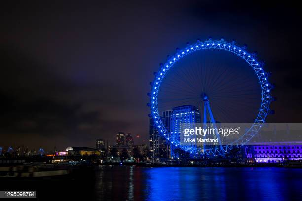 The London Eye is lit up blue in Support Of The NHS on January 07, 2021 in London, England. In a renewed gesture of thanks to the NHS workers and...