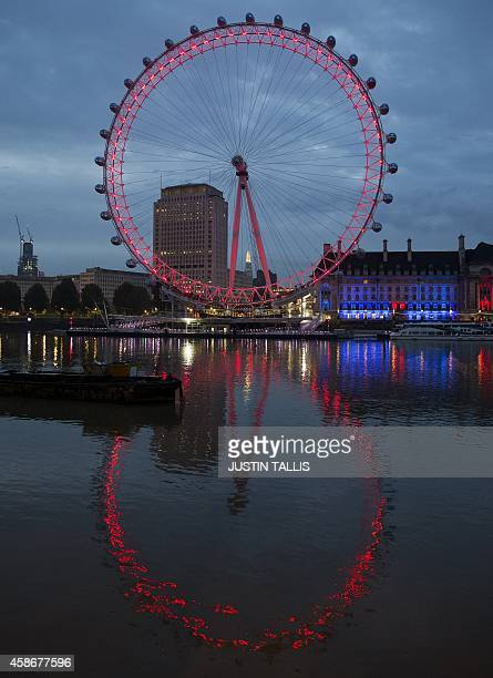 The London eye is lit up red reflected in the river Thames in the early morning on Remembrance Sunday in central London on November 9 2014 Queen...
