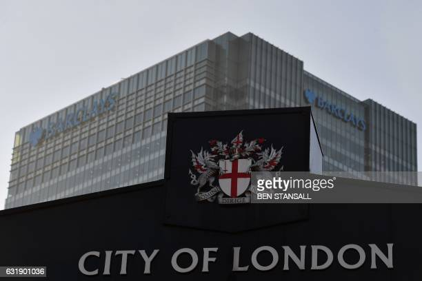 The London head office of Barclays bank is pictured beyond a City of London sign at Billingsgate Fish Market in the financial district of Canary...
