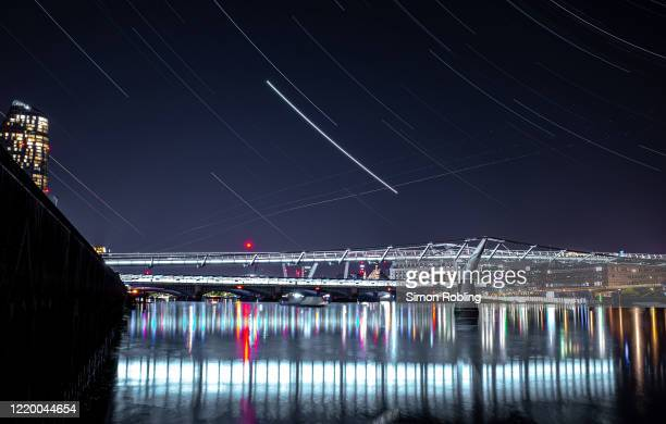 The London Millennium Footbridge is illuminated under the stars on a clear night on April 21, 2020 in London, England. The clear skies created by the...