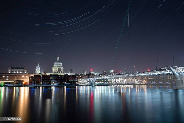 The London Millennium Footbridge is illuminated under the stars on a clear night on April 22, 2020 in London, England. The clear skies created by the...