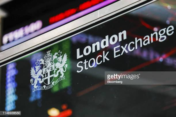 The London Stock Exchange logo sits in front of FTSE 100 Index share price information in the atrium of the London Stock Exchange Group Plc's offices...