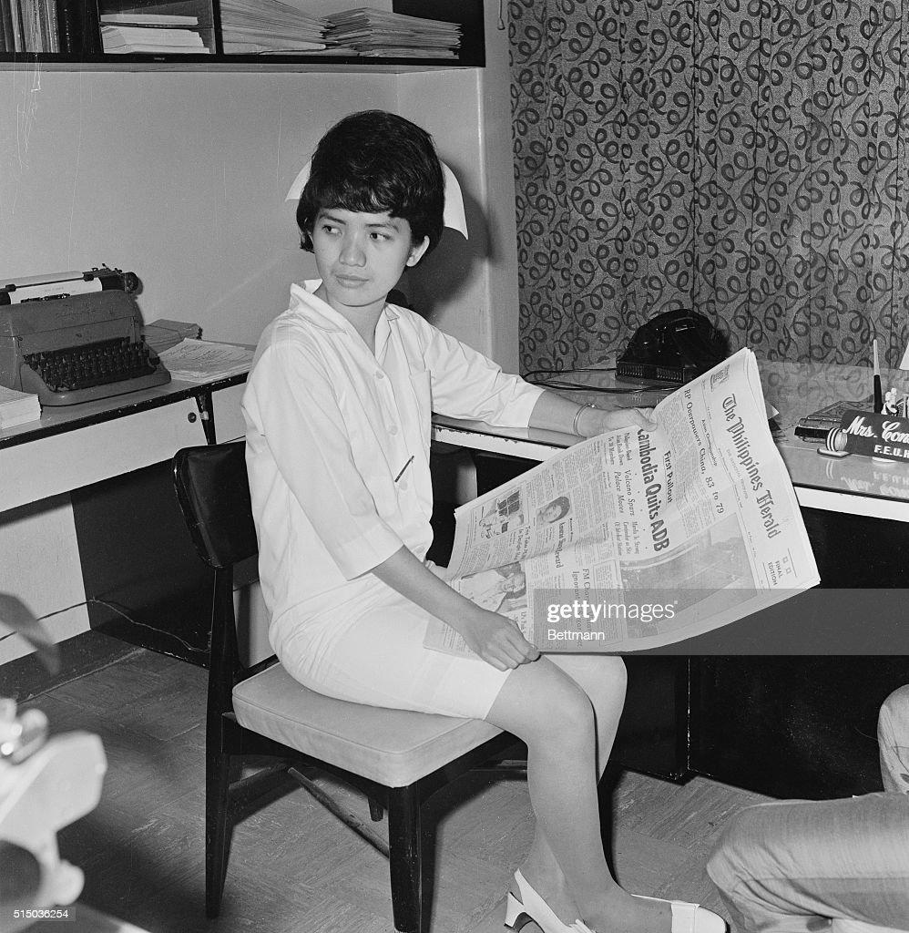 Corazon Amurao Reading a Newspaper : News Photo