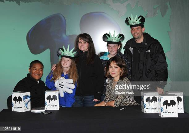 The Lopez family of Seattle WA receive the first copy of Disney Epic Mickey for Wii game with Kyle Massey and Jennifer Grey pose at the launch of...