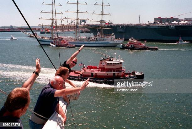 The Lord Nelson crew wave to the neighboring ships the USS John F Kennedy and the MIR while closing into the Boston Harbor during Sail Boston on July...