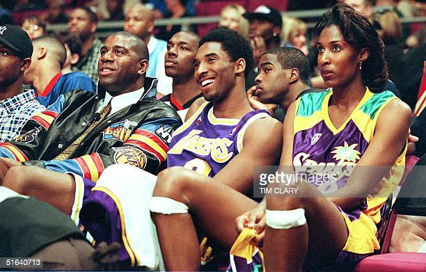 The Los Angeles 2ball team of Los Angeles Lakers' Kobe Bryant and Lisa Leslie sit on the bench with their coach Magic Johnson the threetime Los...