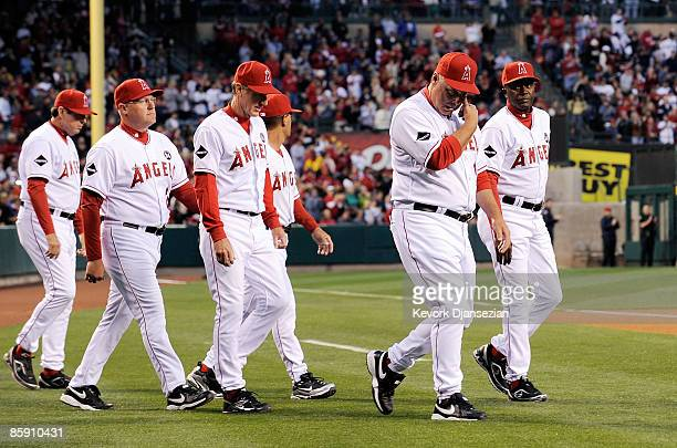 The Los Angeles Angels coaching staff lead by manager Mike Scioscia walk to line up for a moment of silence for Angels rookie pitcher Nick Adenhart...