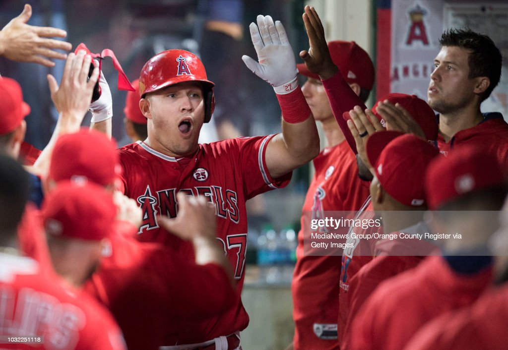 6be02b0a6 The Los Angeles Angels Mike Trout high-fives teammates in the dugout after  scoring on