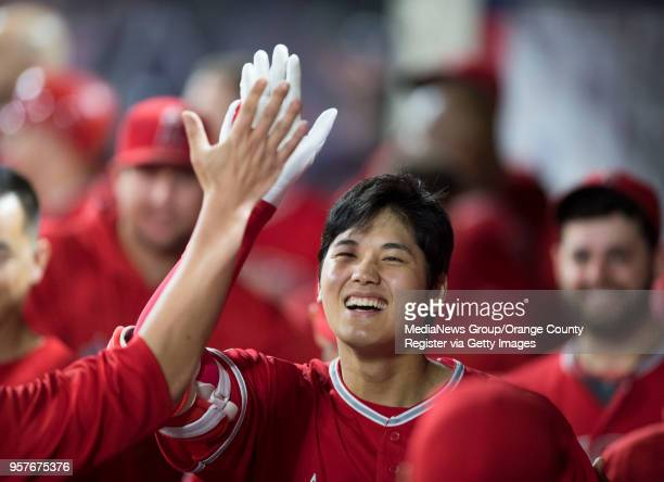 The Los Angeles Angels' Shohei Ohtani is congratulated in the dugout after his seventh inning home run against the Minnesota Twins at Angel Stadium...