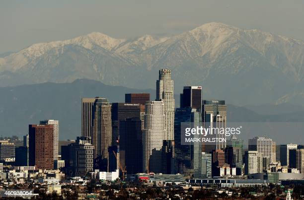 The Los Angeles city skyline stands in front of the snow covered San Gabriel Mountains after a snowstorm hit the region on December 31 2014 Two...