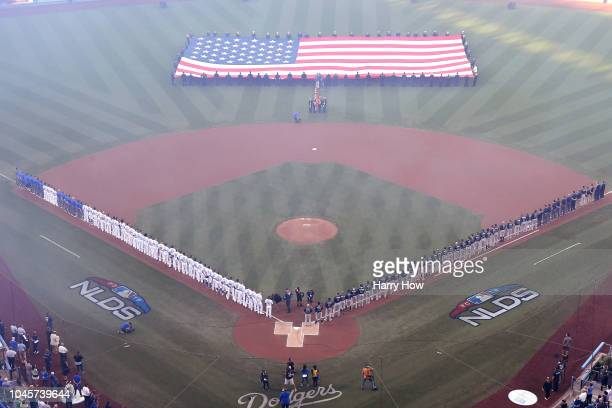 The Los Angeles Dodgers and the Atlanta Braves stand for the national anthem prior to Game One of the National League Division Series at Dodger...