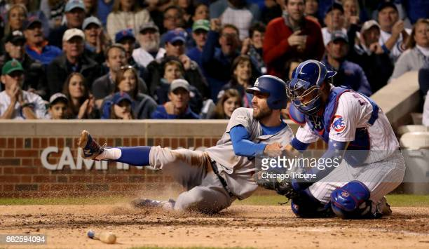 The Los Angeles Dodgers' Chris Taylor is tagged out a the plate by Chicago Cubs catcher Wilson Contreras right in the fifth inning during Game 3 of...