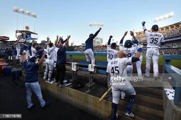The Los Angeles Dodgers dug out celebrate after Max Muncy hit a two run home run in the first inning of game five of the National League Division...