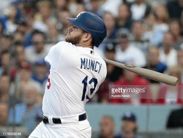 The Los Angeles Dodgers' Max Muncy hits a home run against the Washington Nationals in the first inning of Game 5 of the National League Division...