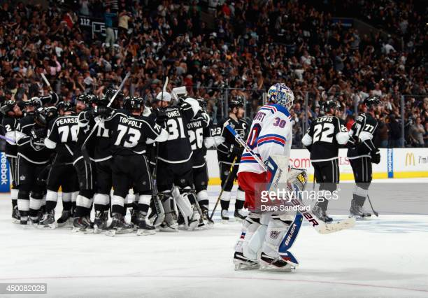 The Los Angeles Kings celebrate winning as Henrik Lundqvist of the New York Rangers skates by after Game One of the 2014 Stanley Cup Final at Staples...