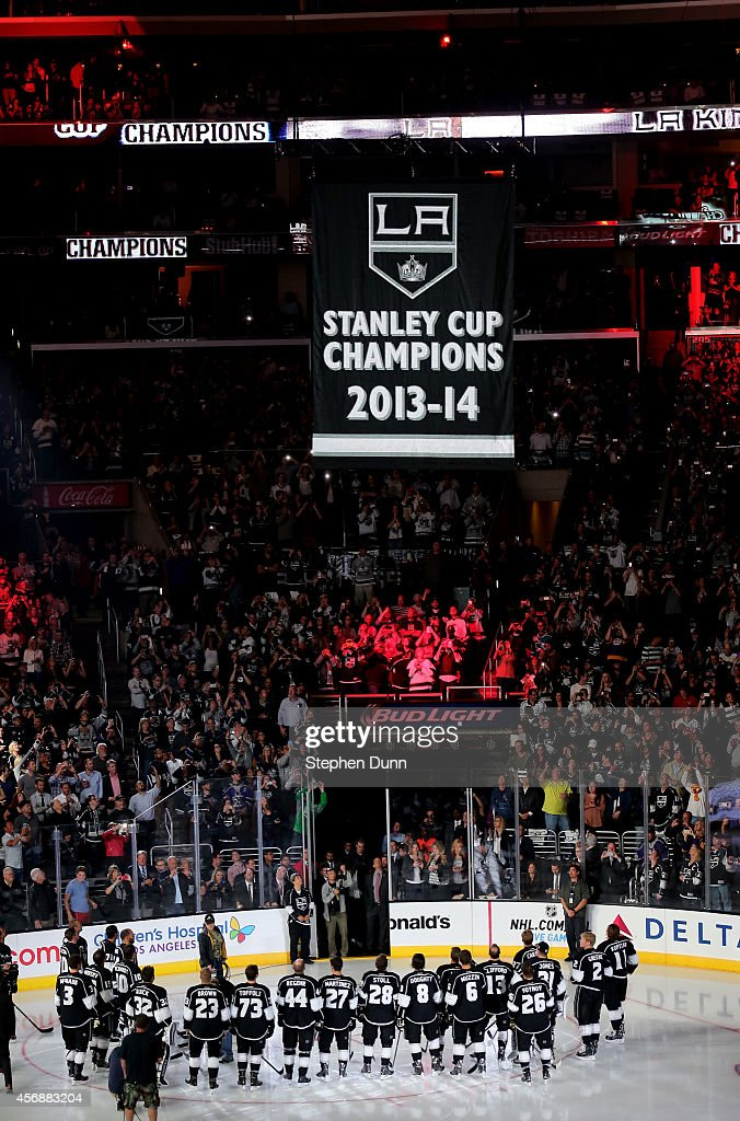 The Los Angeles Kings stand on the ice as the Stanley Cup Championship banner is raised to the rafters during ceremonies before the game with the San Jose Sharks in their NHL season opener at Staples Center on October 8, 2014 in Los Angeles, California.