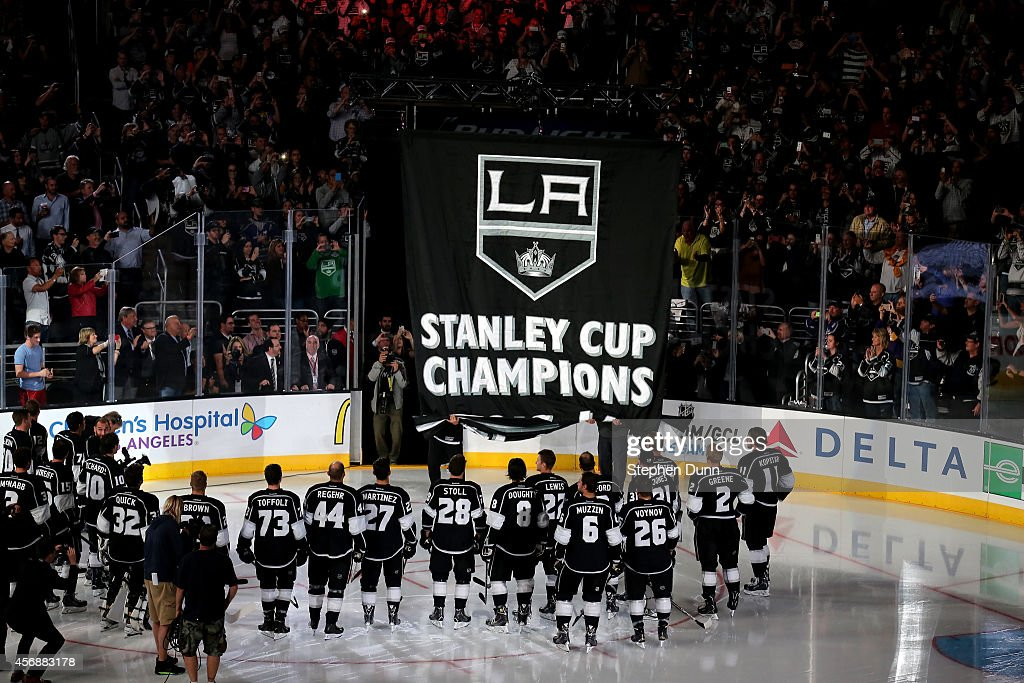 The Los Angeles Kings stands on the ice as the Stanley Cup Championship banner is unfurled during ceremonies before the game with the San Jose Sharks in their NHL season opener at Staples Center on October 8, 2014 in Los Angeles, California.