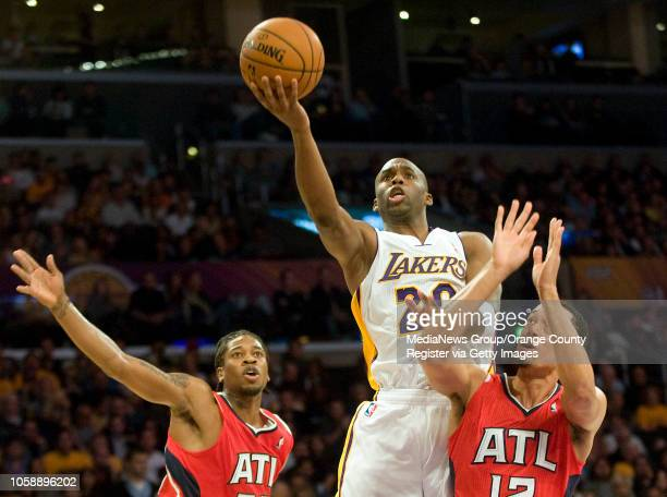 The Los Angeles Lakers' Jodie Meeks goes over the Atlanta Hawks' Cartier Martin left and John Jenkins at Staples Center in Los Angeles CA on November...