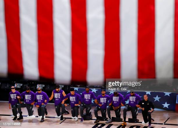 The Los Angeles Lakers kneel during the National Anthem wearing VOTE shirts prior to the start of the game against the Denver Nuggets in Game Two of...