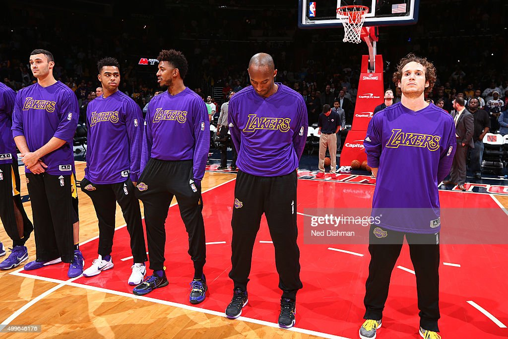 The Los Angeles Lakers stand for a moment of silence during the National Anthem before the game against the Washington Wizards on December 2, 2015 at Verizon Center in Washington, DC.