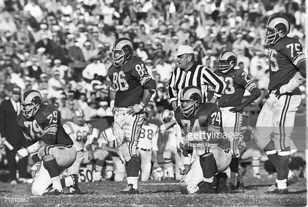 The Los Angeles Rams defensive line rests on the field during a pause in play in a game against the San Francisco 49ers 1963 Pictured are Stan...