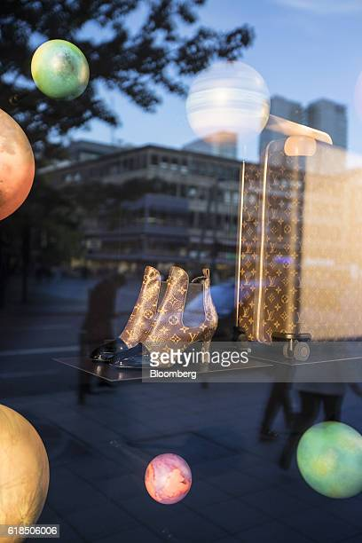 The Louis Vuitton logo adorns a pair of womens luxury leather revival ankle boots and a wheeled horizon suitcase as they sit in the window display of...