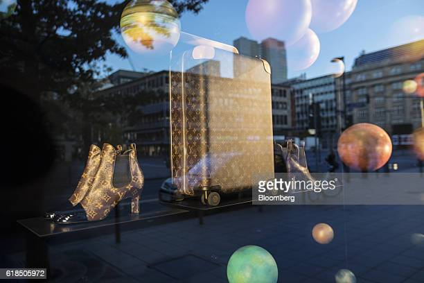 The Louis Vuitton logo adorns pairs of womens luxury leather revival ankle boots and a wheeled horizon suitcase as they sit in the window display of...