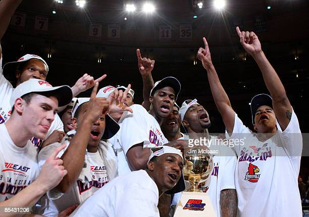 The Louisville Cardinals celebrate with the trophy after defeating the Syracuse Orange during to win championship game of the Big East Tournament at...