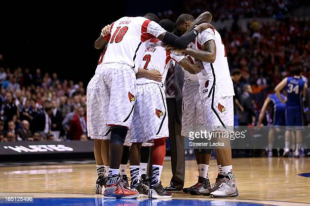 The Louisville Cardinals huddle up on the court after teammate Kevin Ware injured his leg in the first half against the Duke Blue Devils during the...