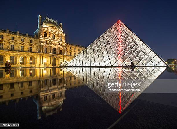 The Lourvre museum with reflection and couple lover at dusk, Paris, France