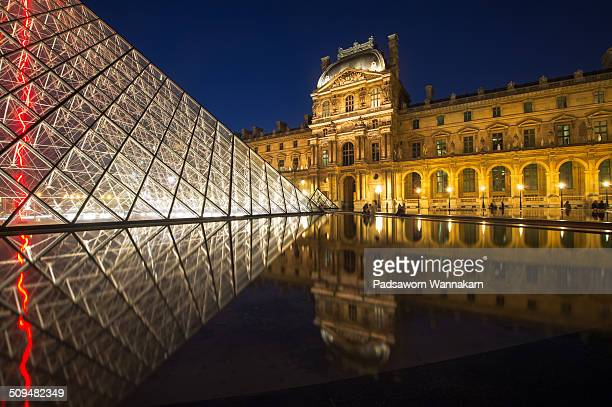 The Louvre museum and reflection at dusk, Paris, France