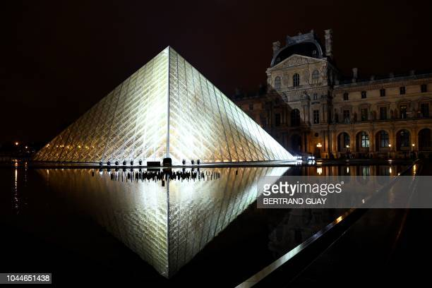 TOPSHOT The Louvre Pyramid is illuminated in the night prior to the Louis Vuitton SpringSummer 2019 ReadytoWear collection fashion show in Paris on...
