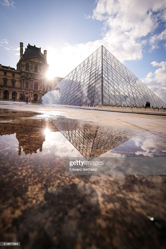 The Louvre Pyramid reflecting into a water puddle, on February 7, 2016 in the 1st quarter of Paris, France.