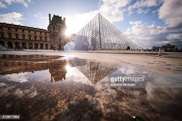 The Louvre Pyramid reflecting into a water puddle on February 7 2016 in the 1st quarter of Paris France