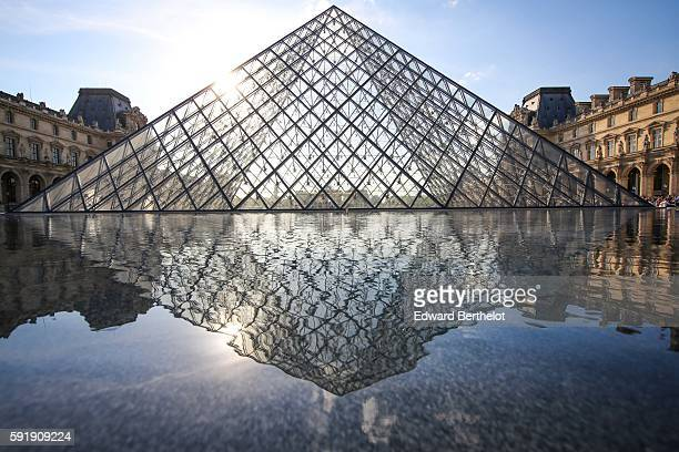 The Louvre pyramid reflects into the water in the sunlight at the Louvre museum in the 1st quarter of Paris on May 7 2016 in Paris France