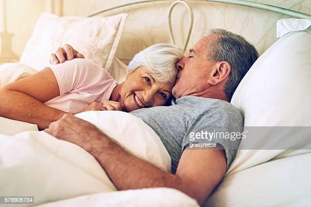 the love that lasted a lifetime - pareja abrazados cama fotografías e imágenes de stock