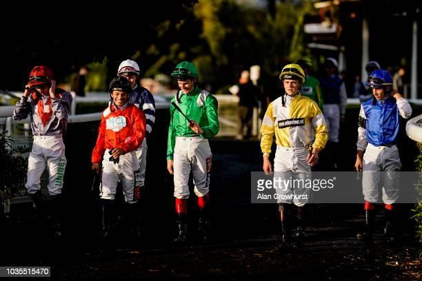 The low sun illuminates the jockeys silks as they enter the parade ring at Kempton Park Racecourse on September 18 2018 in Sunbury United Kingdom