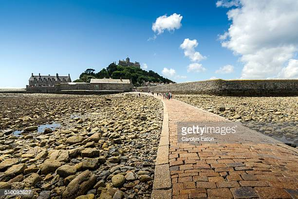 The low tide exposes the rocks on the sea bed and the causeway used for centuries by visitors to St Michael's Mount in Cornwall. A castle tops the...