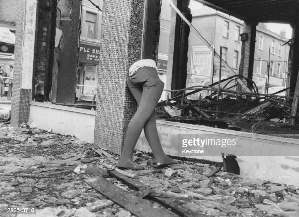 The lower half of a mannequin stands among the debris of a destroyed shop after a night of violence during rioting in Brixton, London, England, 13th...