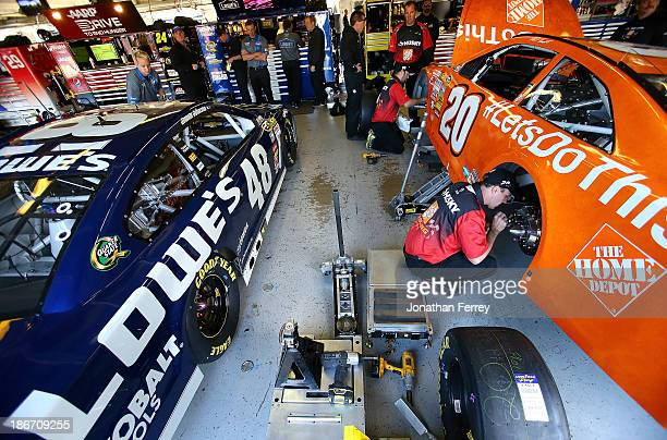 """The Lowe's Chevrolet, driven by Jimmie Johnson, and the Home Depot """"Let's Do This"""" Toyota, driven by Matt Kenseth, are seen in the garage prior to..."""
