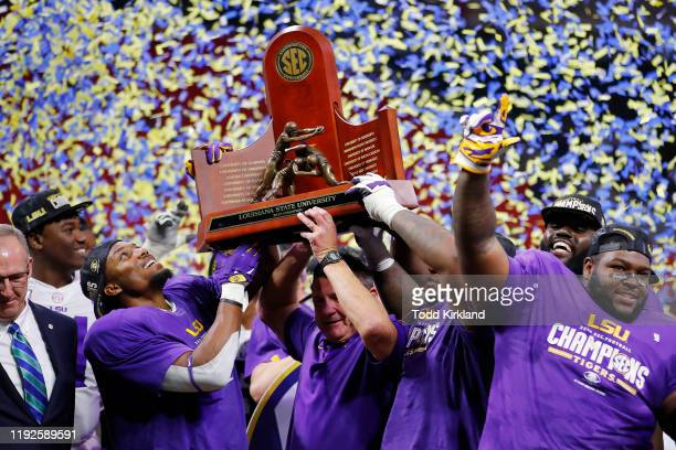 The LSU Tigers celebrate with the trophy after defeating the Georgia Bulldogs 3710 to win the SEC Championship game at MercedesBenz Stadium on...