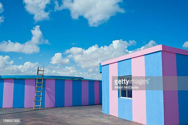 The ludic, bubble-gum pink and blue striped buildings seem unreal. There's no one around and a ladder that reaches straight up to to the bright blue...