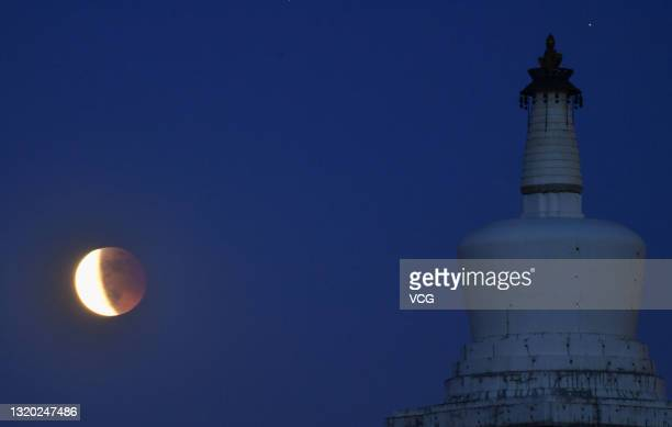 The lunar eclipse is observed over the White Dagoba at Beihai park on May 26, 2021 in Beijing, China.