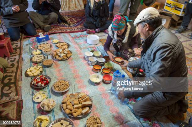 The lunch spread with a Kazakh woman preparing traditional suutei tsai in the kitchen of the winter camp in the Sagsai Valley in the Altai Mountains...