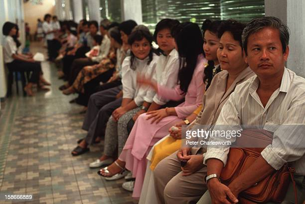 The Luong family wait in a corridor for an interview with American Immigration and Naturalization Service officials who will determine whether they...