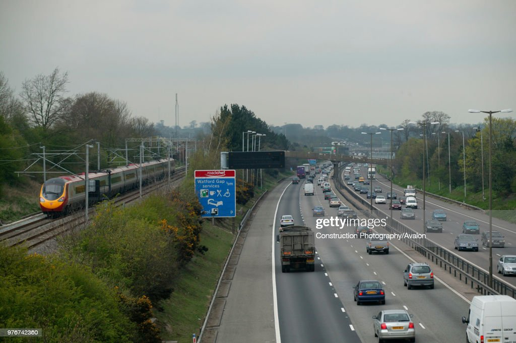 The M1 motorway at Watford Gap as a north bound Virgin Trains Pendolino on the West Coast Main Line races the traffic on a trip to the north. April 2005 : News Photo